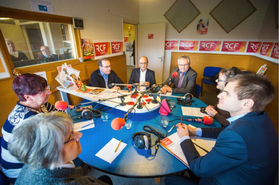 Table ronde en janvier 2020 : les journalistes et personnes interviewées, équipées de micros et de leurs notes, sont autour d'une table ronde