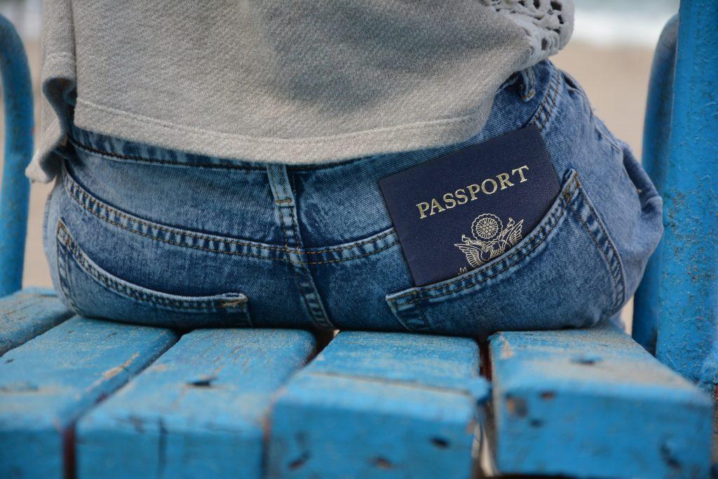 Une personne assise de dos avec un passeport dépassant de la poche arrière de son jean