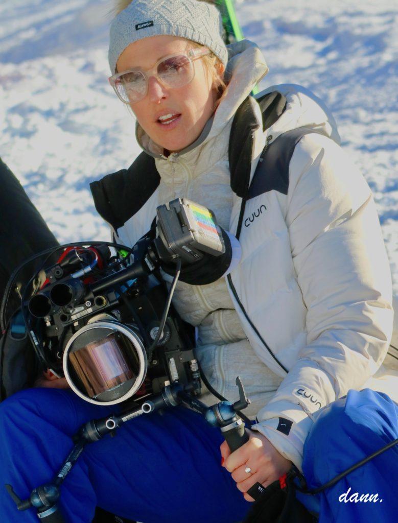Charlène favier, cinéaste, tenant sa caméra dans la neige sur le tournage de Slalom - photo portrait