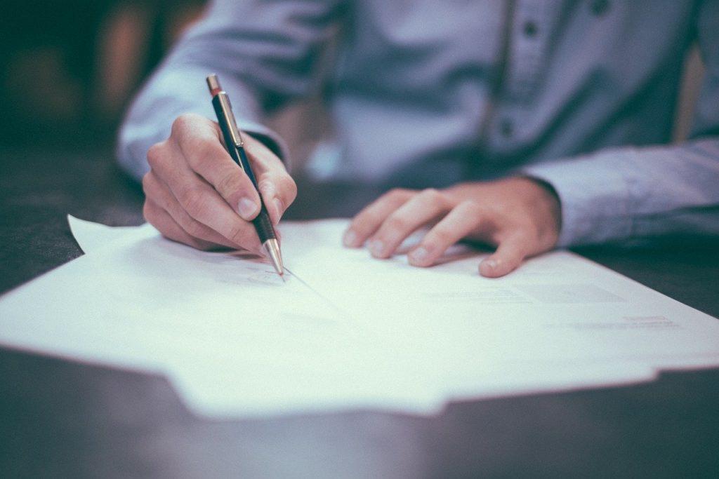 un homme en chemise signe des papiers sur un bureau