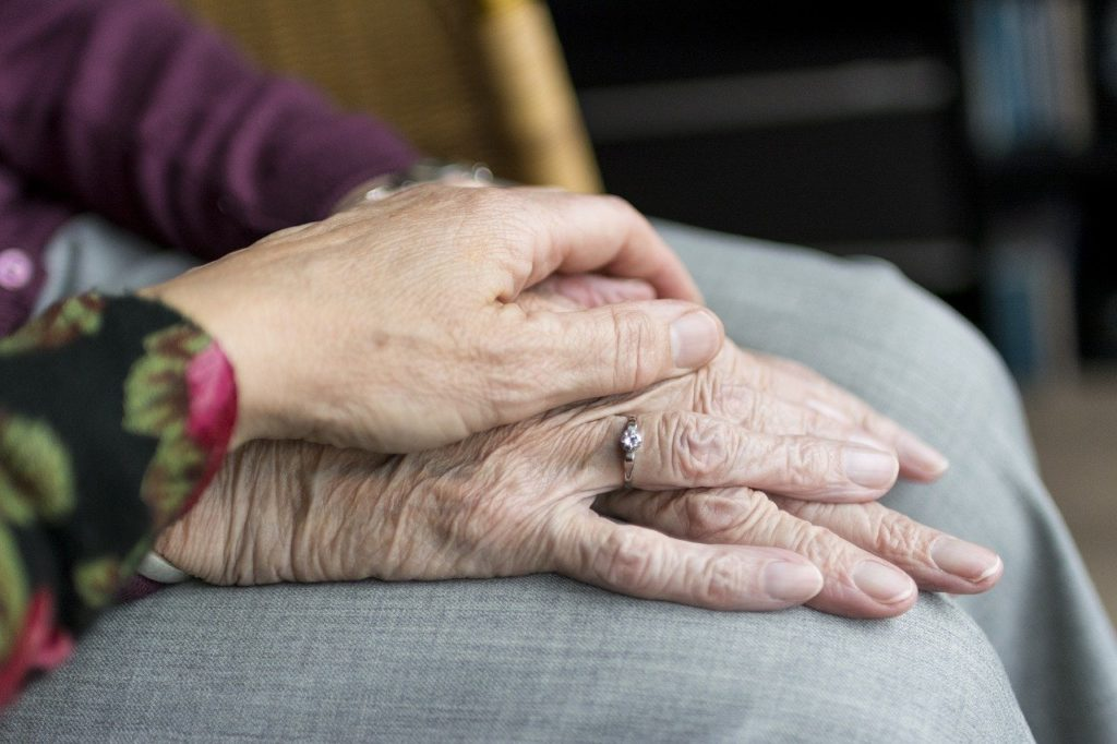 mains d'une personne jeune posée sur celles d'une personne âgée en soutien