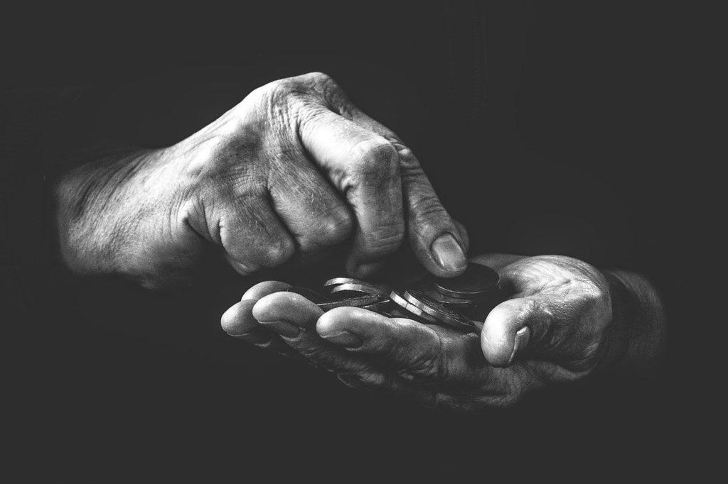 photo en noir et blanc, des mains d'hommes comptent les pièces qu'il tient
