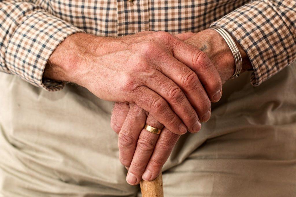 les mains d'un homme âgé tiennent sa canne fermement